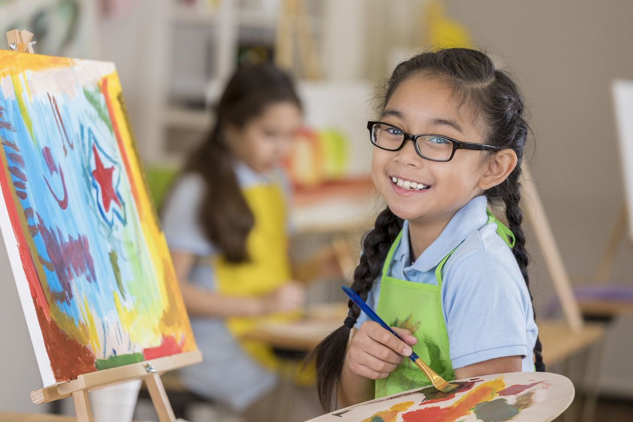 young asian girl painting at an easel