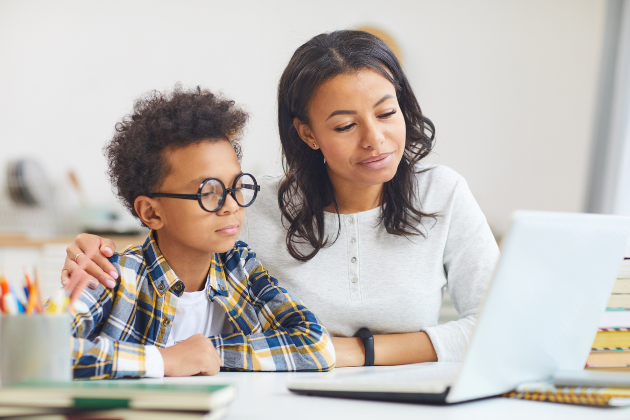 Mother and son using a laptop for telehealth