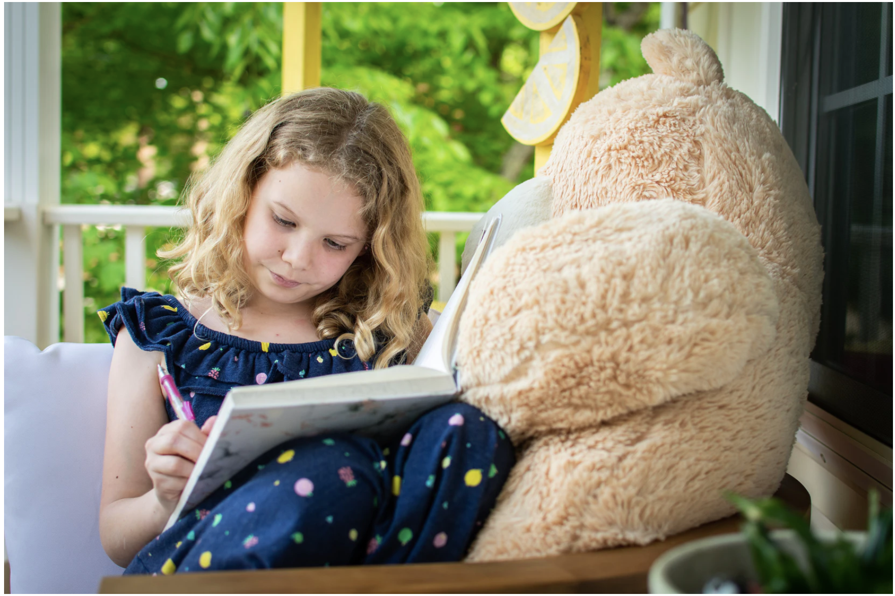 Little girl writing in a journal next to a teddy bear